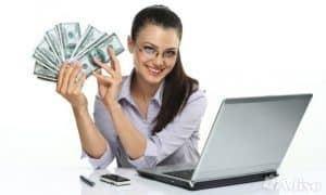 Direct Loan Lender girl holding cash in hand at a laptop