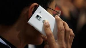 Contract Phones No Credit Check man using phone next to his face